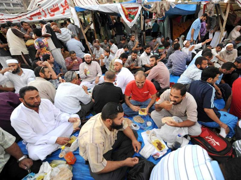 Egyptian supporters of deposed president Mohamed Morsi break their fasting during Ramzan in Cairo as they continue to hold a sit-in outside Rabaa al-Adawiya mosque. (AFP photo)