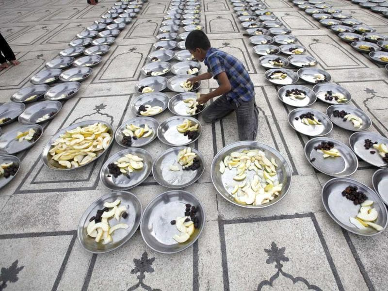 A volunteer prepares plates for Iftar during the holy month of Ramzan at a mosque in Karachi. (Reuters photo)