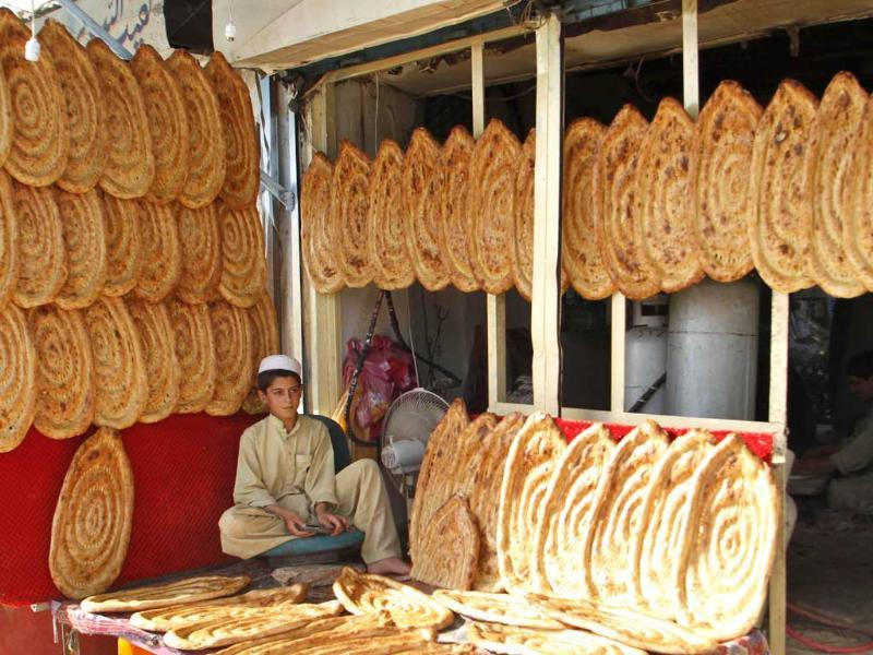 A youth selling bread waits for customers in his shop ahead of the holy month of Ramzan in Kandahar, Afghanistan. (AP photo)