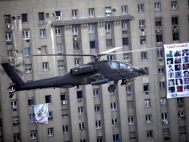 An Egyptian Army helicopter flies over thousands of supporters of Egypt's top military officer, Gen. Abdel-Fatah el-Sissi during a rally in Tahrir Square in Cairo, Egypt, Friday, July 26, 2013. (AP Photo)