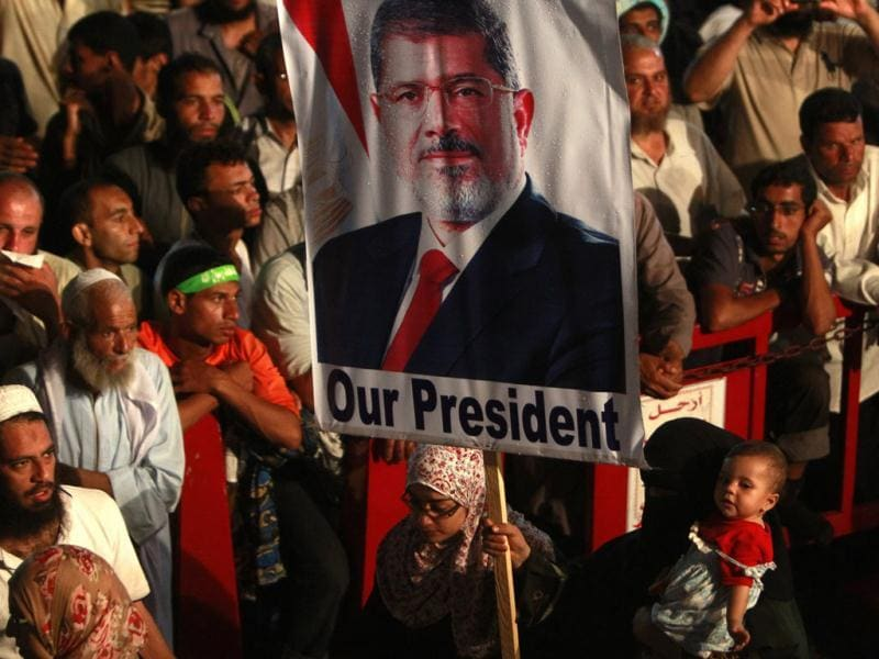 A supporter of deposed Egyptian President Mohamed Morsi holds a Morsi banner while taking part in a protest at the Rabaa Adawiya square, where Morsi supporters are camping, in Cairo. (Reuters)