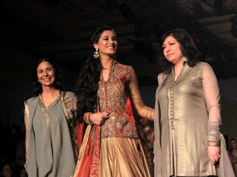 Nargis walks the ramp with the designer duo.