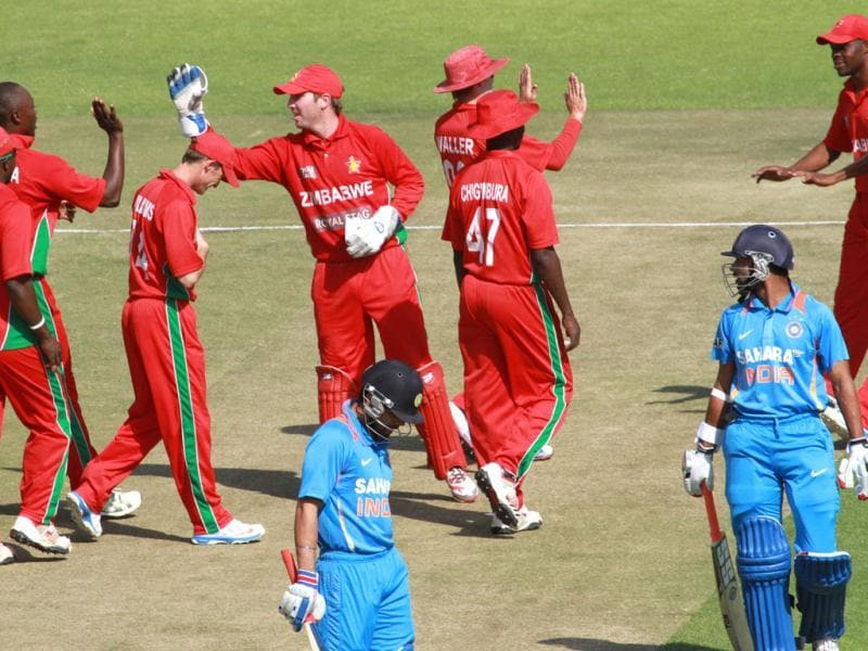 Zimbabwean players celebrate the wicket of India's Rohit Sharma (R) during their third ODI, in Harare. (AP Photo)