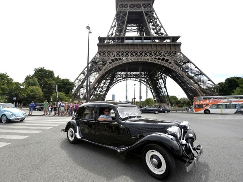 A Citroen Traction Avant passes the Eiffel tower in Paris during a vintage cars parade as part of the sixth