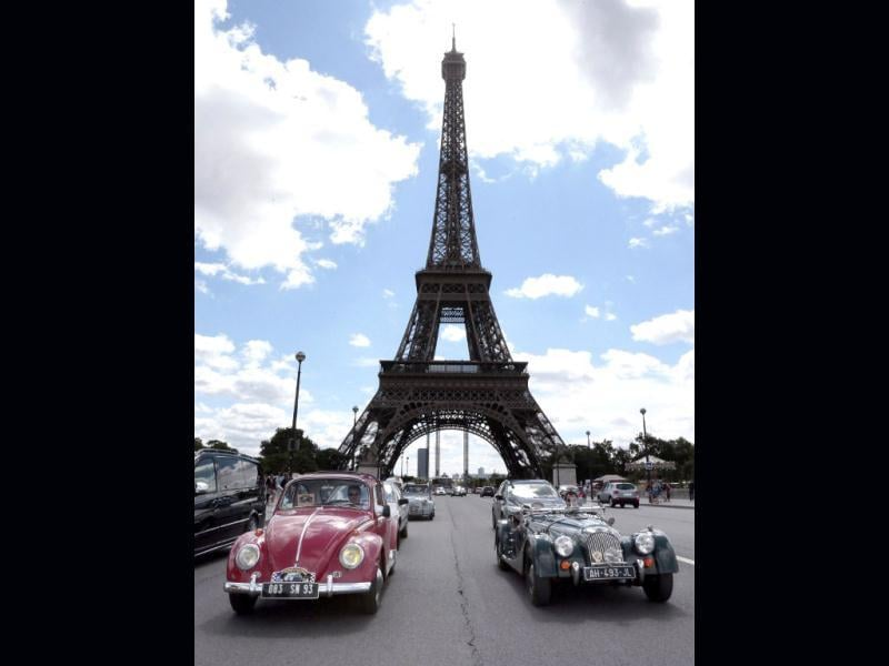 A Coccinelle Volkswagen (L) and a Morgan (R) pass by the Eiffel tower in Paris during the