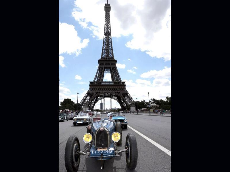 A Bugatti passes by the Eiffel tower in Paris during the