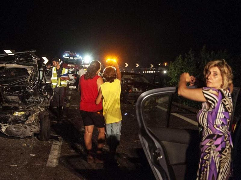 People and rescuers stand by smashed cars on highway near Avellino, southern Italy. (AP Photo)