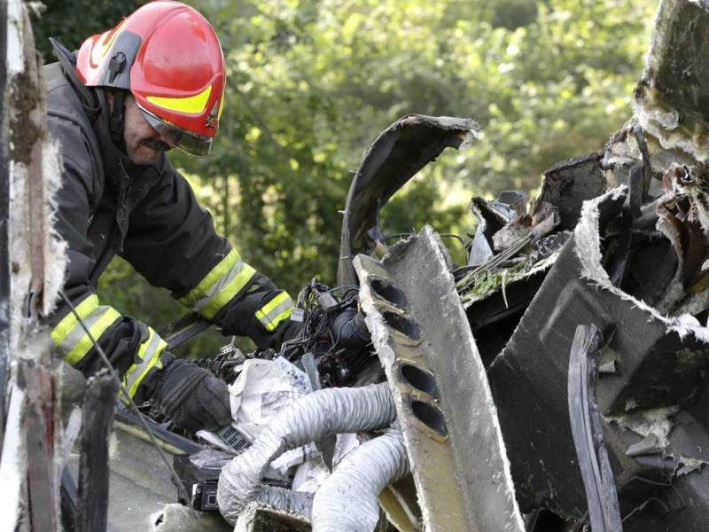 A firefighter searches through the wreckage of a bus which crashed near Avellino, southern Italy. (AP Photo)