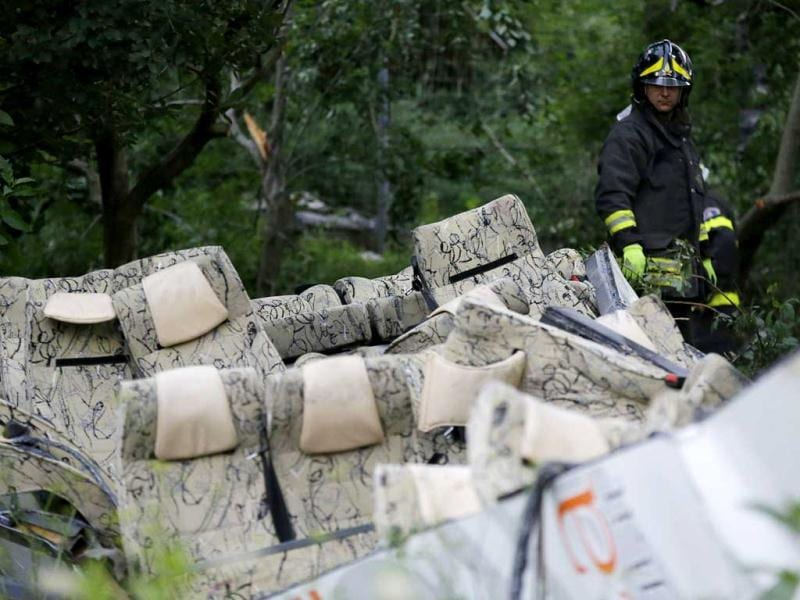 A firefighter looks at the wreckage of a bus following a crash near Avellino, southern Italy. (AP Photo)