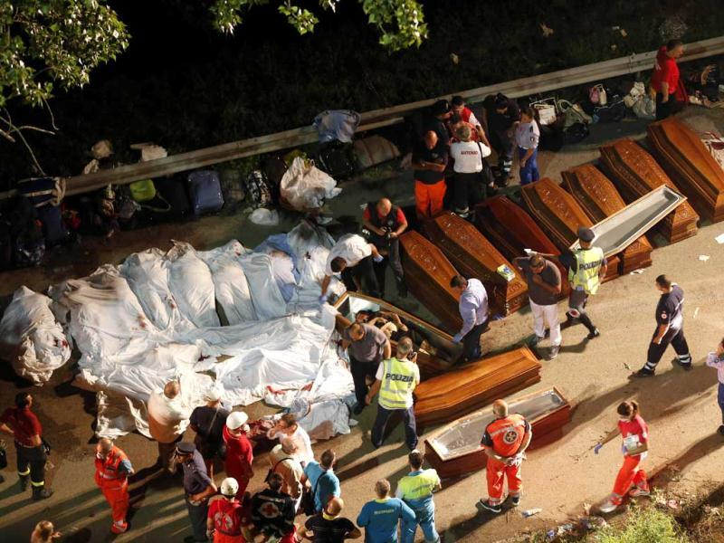 Coffins are lined up near the wreckage of a bus following a crash near Avellino, southern Italy. (AP Photo)