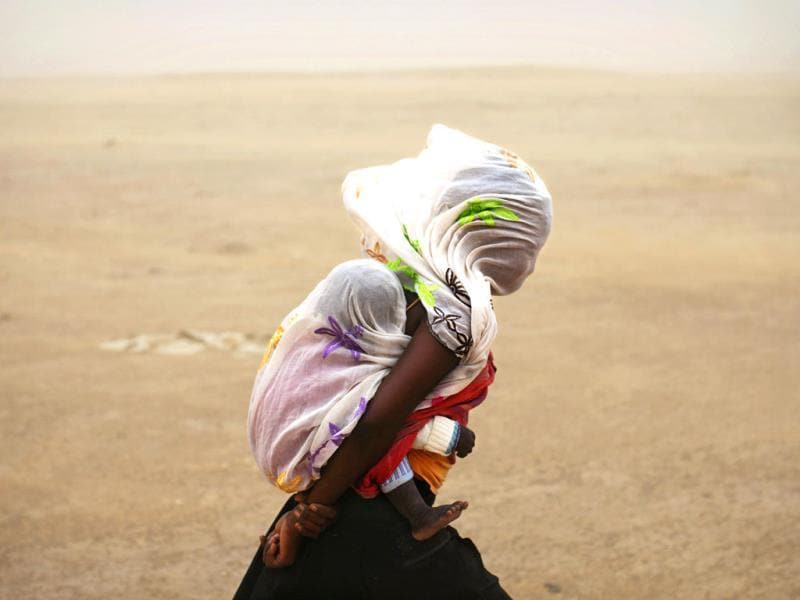 A woman carrying her baby and wrapped with a shawl walks through a sandstorm in Timbuktu. (Reuters Photo)