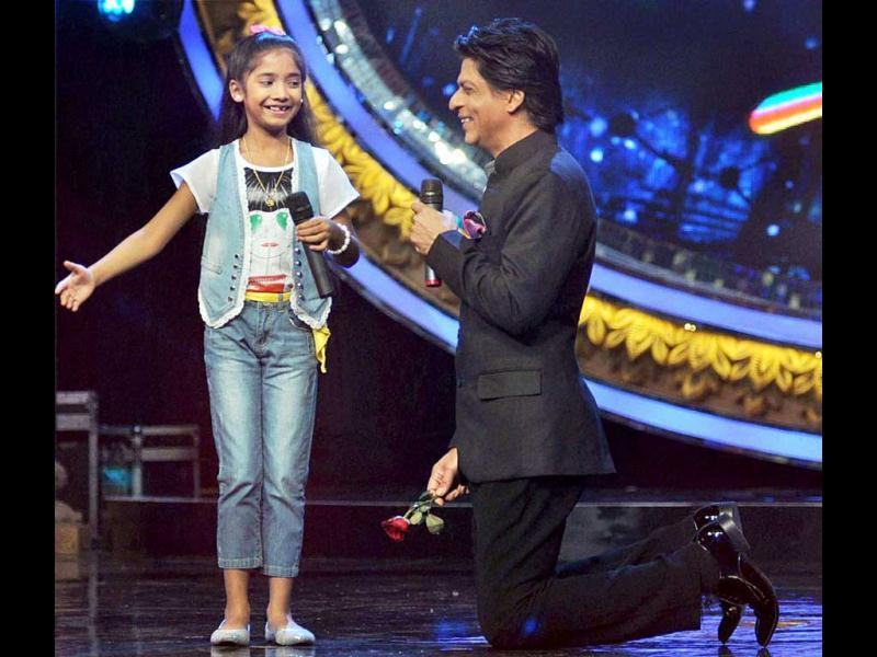Shah Rukh Khan interacts with a contestant on the sets of a TV show in Mumbai on Sunday. (PTI Photo)