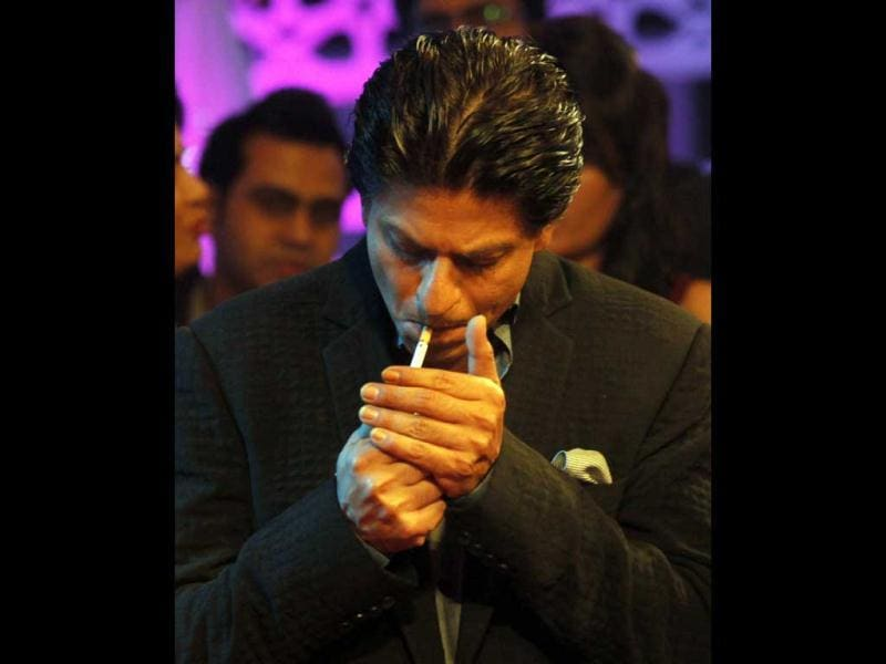 Shah Rukh Khan was even caught lighting a cigarette while promoting his Chennai Express in Mumbai. (AP Photo) (HT does not promote smoking cigarettes.)