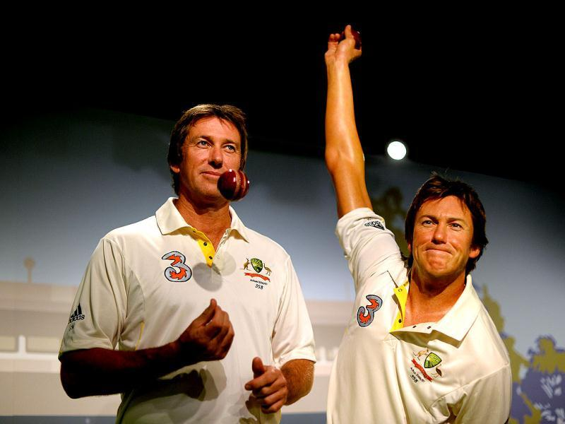 Australia's cricket legend Glenn McGrath (L) tosses a ball as he poses for photos during the launch of his wax figure at Madame Tussauds in Sydney. (AFP Photo)