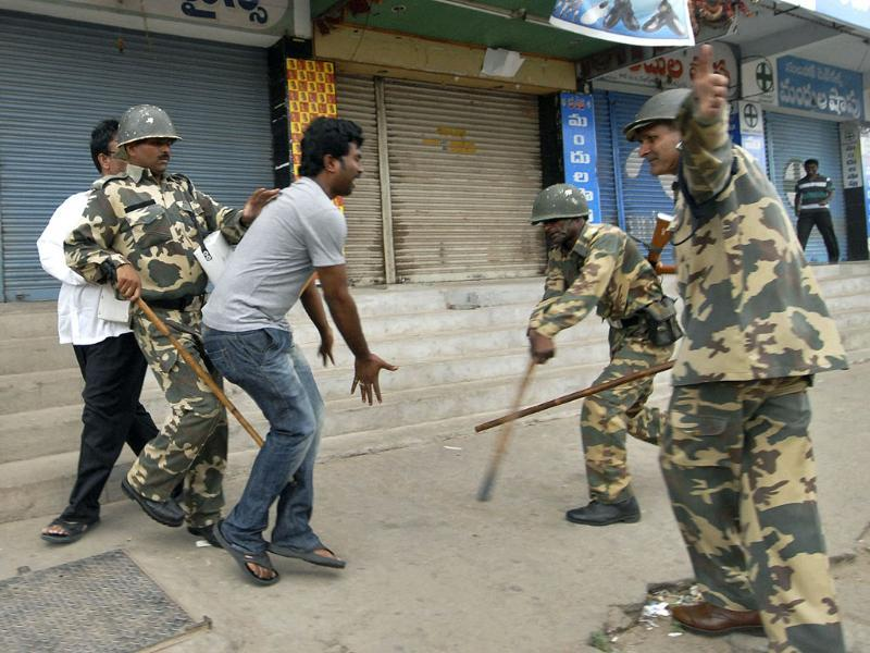 Security officers use batons to charge at a man protesting after UPA endorsed the formation of Telangana. (AP photo)