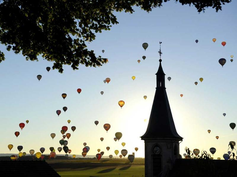 Hot-air balloons fly near a church over Chambley-Bussieres, eastern France to try to set a world record with 408 balloons in the sky, as part of the yearly event of international air-balloon meeting. (AFP photo)