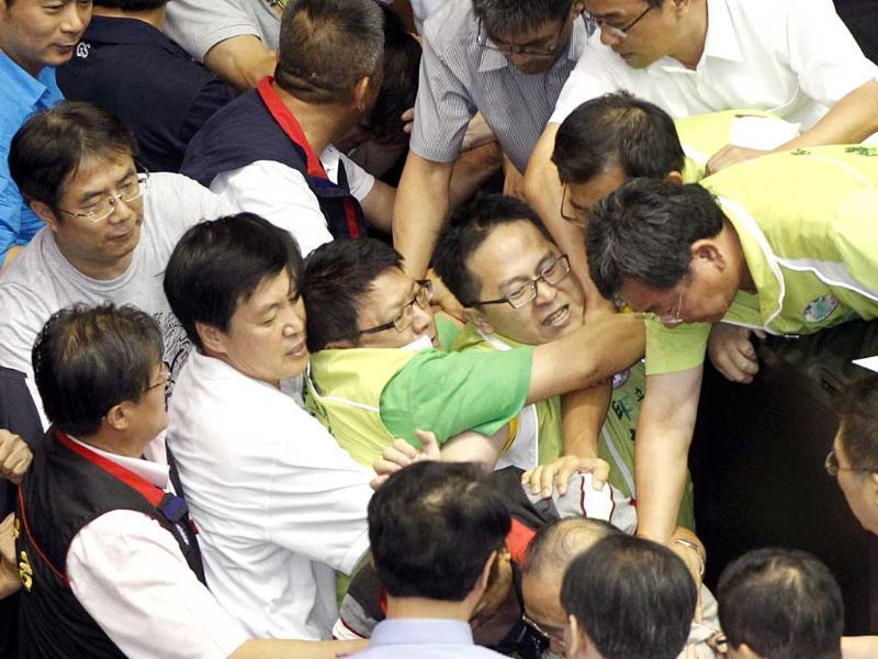 Ruling and opposition lawmakers fight on the legislature floor in Taiwan. They exchanged punches and threw water at each other ahead of an expected vote. (AP Photo)