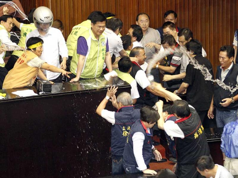 Ruling and opposition lawmakers toss drinks during fight on the legislature floor in Taipei, Taiwan ahead of an expected vote. (AP Photo)