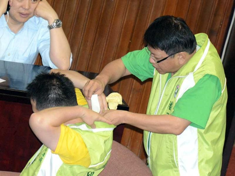 A legislator from the opposition Democratic Progressive Party, helps to paste a medicated pack onto his colleague Chu Chih-wei's neck after a fight before a vote is taken. AFP photo