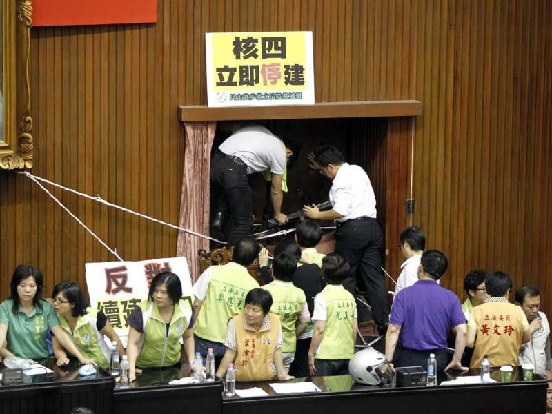 Opposition lawmakers block a door of the legislature floor in Taipei, Taiwan as they exchanged punches ahead of an expected vote. (AP Photo)