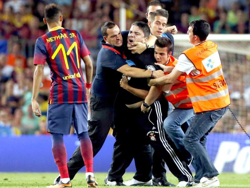 Security officers grab a man who jumped onto the field as Barcelona's Neymar looks on, during the Joan Gamper trophy soccer match against Santos at the Nou Camp in Barcelona. (Reuters)