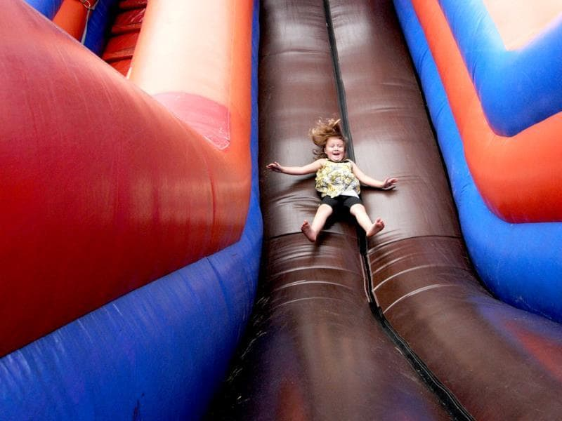 Kyleigh Machado, 4, takes a turn on the inflatable slide during the Glad-Peach Festival held in downtown Coloma, Michigan.(AP Photo)