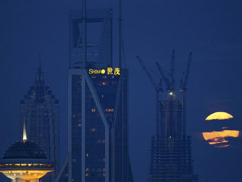 Moon rises over the skyline next to the Shanghai Tower undergoing construction at Pudong financial district in Shanghai. (Reuters Photo)