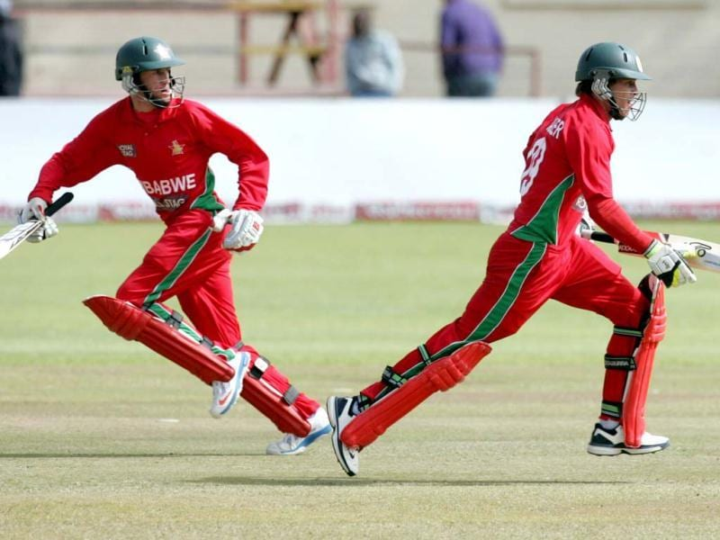 Zimbabwe's captain Brendan Taylor (R) runs with teammate Sean Williams during the final ODI against India at the Queens Sports Club in Bulawayo. (AFP Photo)