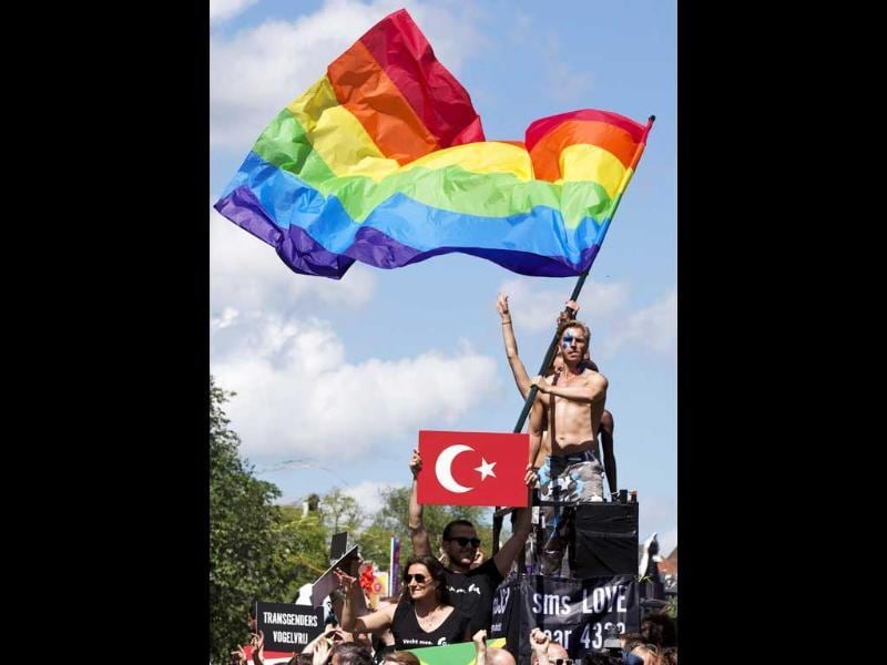 Participants waving a gay pride flag and displaying a placard showing an emblem of the Turkish flag, stand on a barge during the annual Gay Canal Parade in Amsterdam. (Reuters)