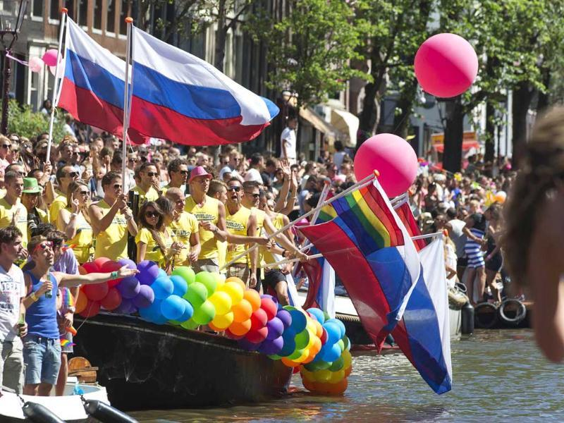 Participants wave Russian and gay pride (C) flags on a barge during the annual Gay Canal Parade in Amsterdam. (Reuters)