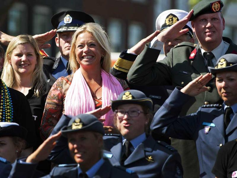 Dutch Defence Minister Jeanine Hennis-Plasschaert (top, 2nd L) stands on a barge with members of the Dutch military during the annual Gay Canal Parade in Amsterdam. (Reuters)
