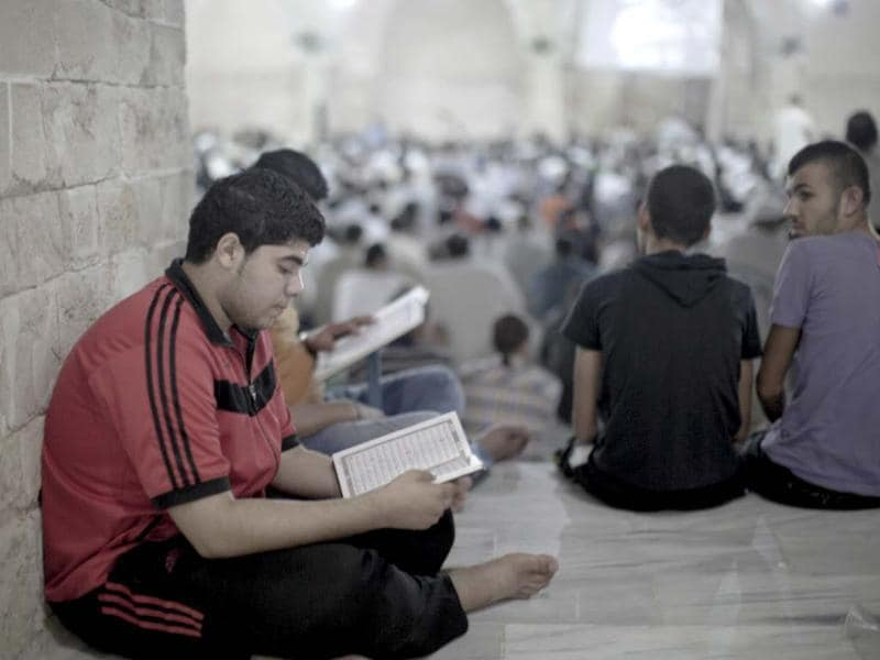Palestinians read verses of the Quran as others pray during Laylat al Qadr prayers on the 27th day of the holy fasting month of Ramzan at Al Emari mosque in Gaza City. (AFP photo)