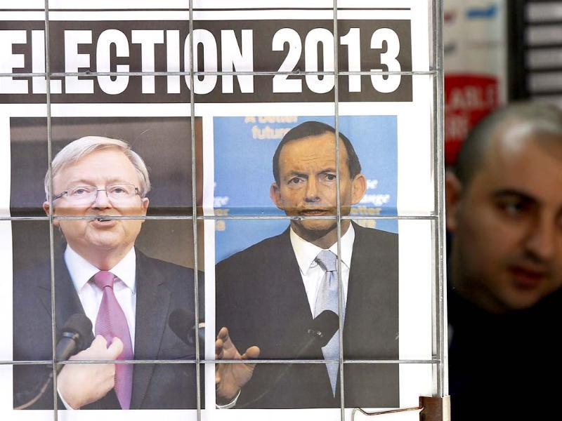 A man walks behind an advertisement for a newspaper with pictures of Australian Prime Minister Kevin Rudd and opposition leader Tony Abbott in central Sydney. (Reuters photo)