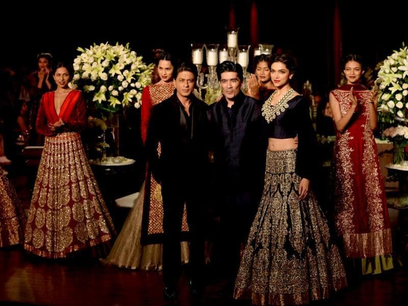 The stars are flanked by designer Malhotra and models.
