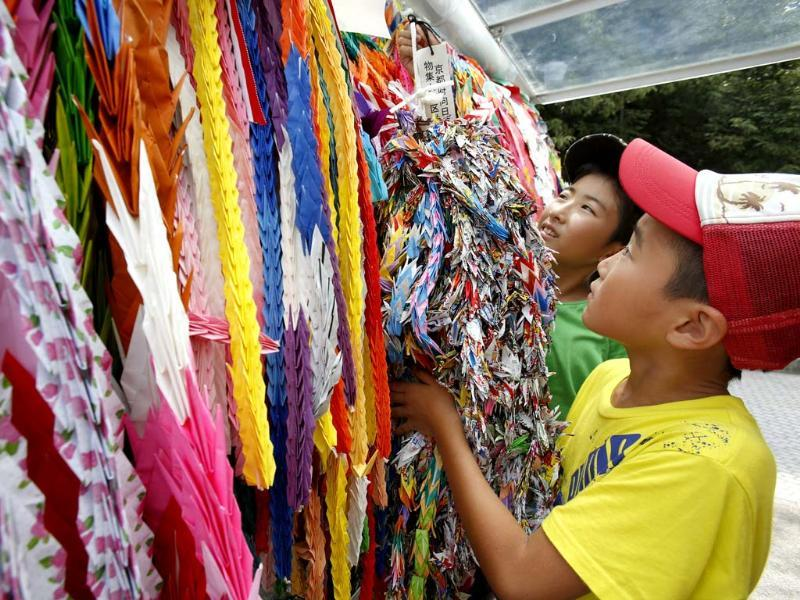 Masaki Namikawa, 11, left, and Keita Deguchi, 9, hang a bundle of paper cranes to add on to thousands of them already placed as a symbolic act dedicated from across the world for world peace at Hiroshima Memorial Peace Park in Hiroshima (AP Photo)