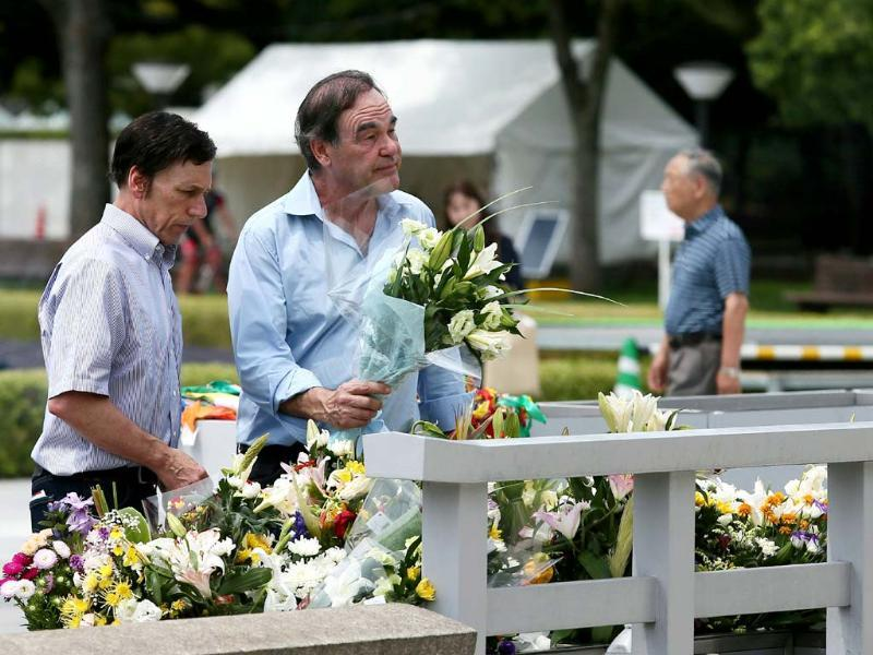 US film director Oliver Stone (front right) places flowers at the cenotaph at the Peace Memoral Park in Hiroshima (AFP Photo)