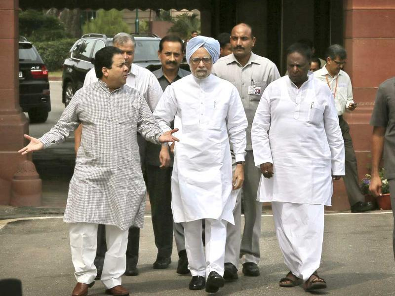 Prime Minister Manmohan Singh talks to his Cabinet members as they walk towards media after his arrival at the opening day of the monsoon session of the parliament, in New Delhi. AP photo