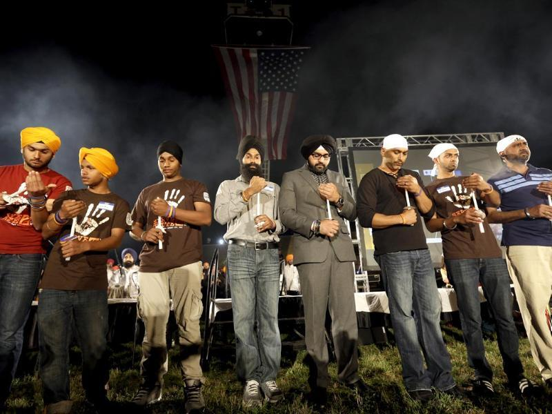 Family members hold candles during a candlelight vigil at the Gurdwara in Wisconsin to mark the one-year anniversary of the shooting rampage that left six dead in Oak Creek, Wisconson. (AP Photo)