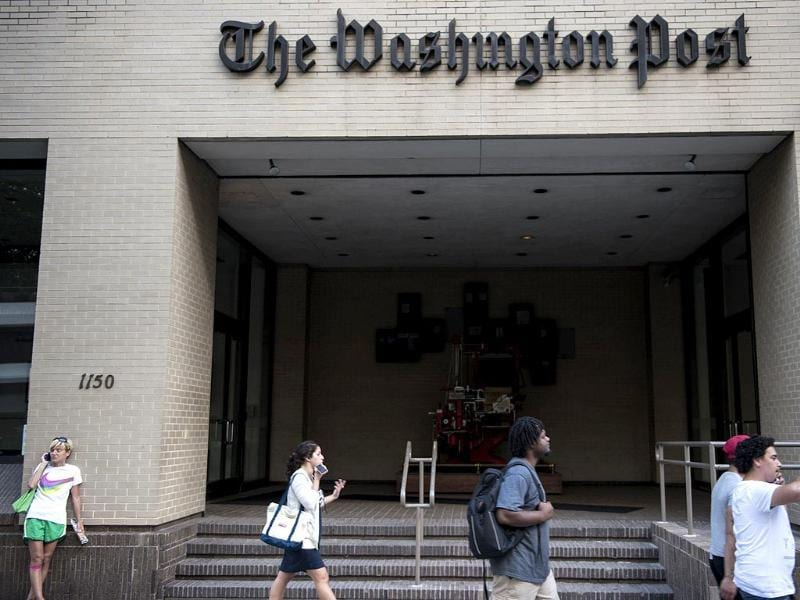 People walk past The Washington Post in Washington, DC after it was announced that Amazon.com founder and CEO Jeff Bezos had agreed to purchase the Post for $250 million. AFP photo