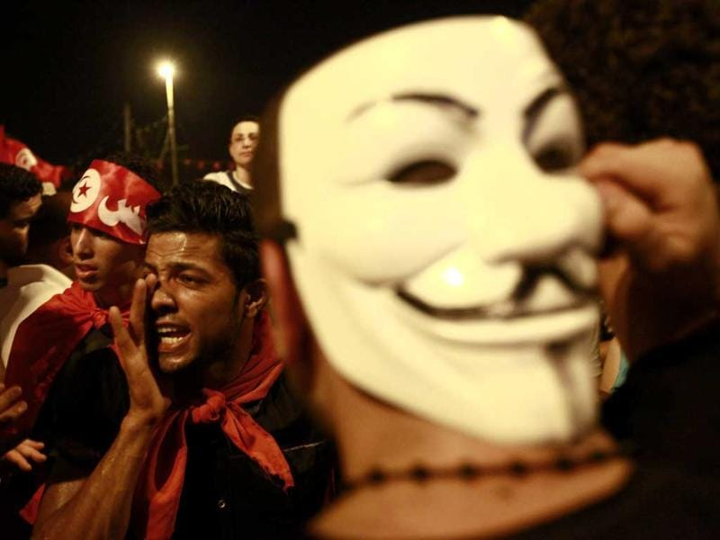 An anti-government protester wears a Guy Fawkes mask as another shouts slogans during a demonstration in Tunis. (Reuters Photo)