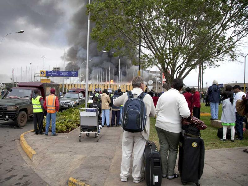 Travelers with his luggage stands on a sidewalk as the fire rages at the international arrivals unit of Jomo Kenyatta International Airport, Nairobi, Kenya. (AP Photo)
