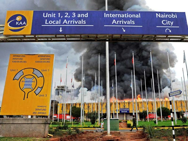 General Service (GSU) officers stand outside the burning Jomo Kenyatta international airport. (AFP Photo)
