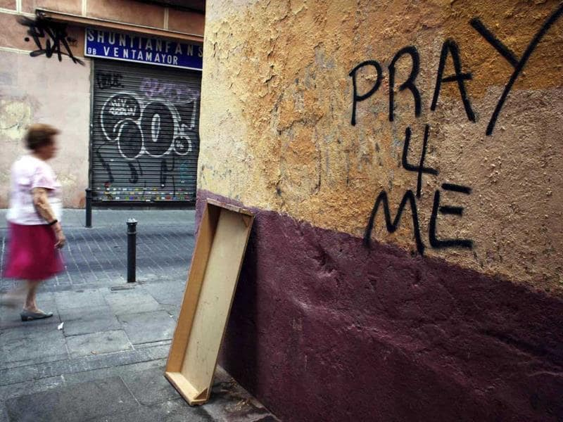 A woman walks past graffiti that reads Pray for me in central Madrid. Reuters photo