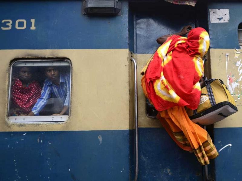 A Bangladeshi passenger climbs on top of a train as other passengers look on from a compartment window as they rush home to their respective villages to be with their families ahead of Eid ul-Fitr in Dhaka. AFP photo
