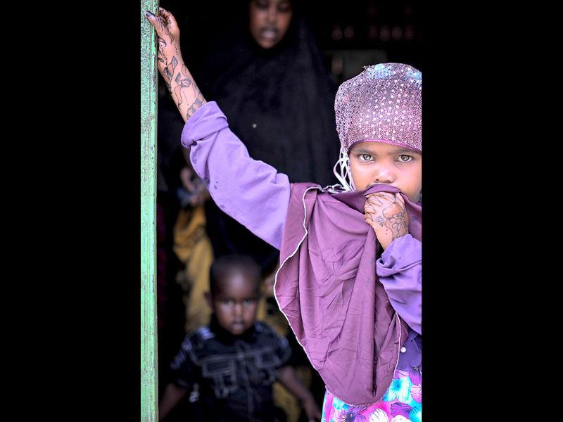 A young girl dressed for the Eid al-Fitr holiday standing in the doorway of a shop in Mogadishu. (AFP Photo)