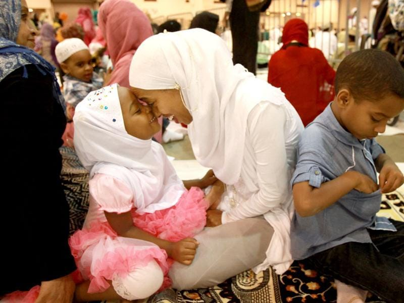 Safia Durri, 3, plays with her mother Hanan Abubeke before the Eid ul Fitr prayer service and celebration at Reliant Center in Houston. (AP Photo)