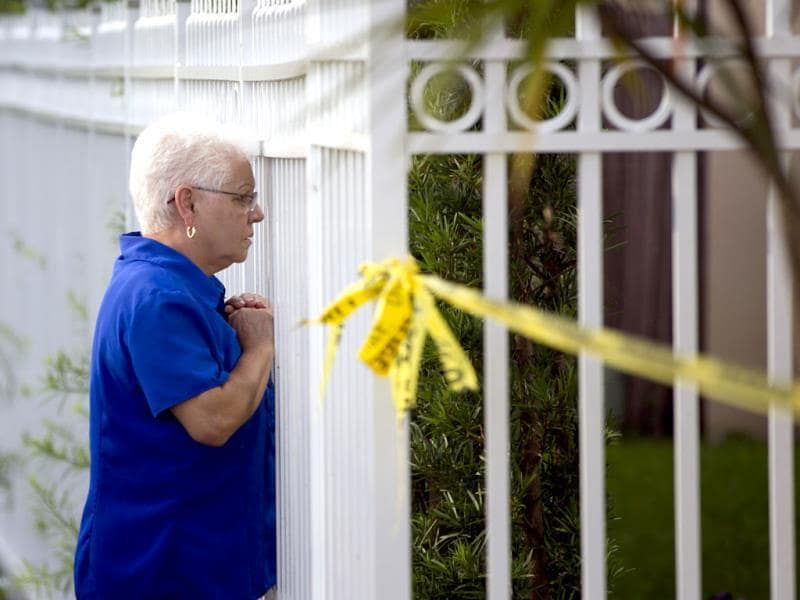 An unidentified woman looks through a fence near a murder scene in Miami where Derek Medina fatally shot his wife and then posted a photo of her body on Facebook. AP Photo