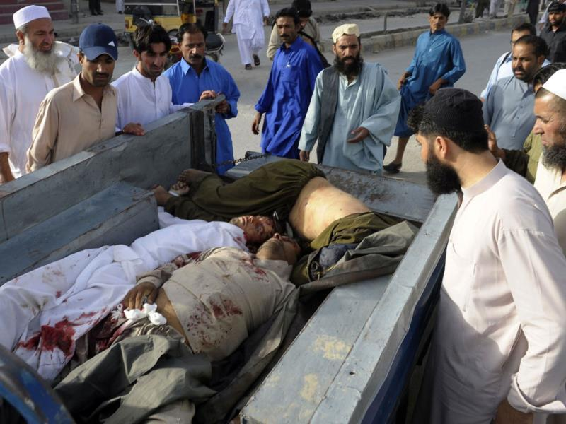Bystanders look at the bodies of worshippers outside a hospital in Quetta following an attack by gunmen on a mosque. AFP