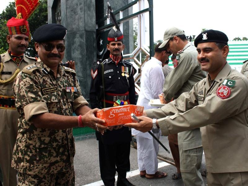 Pakistani Rangers Wing Commander Adnan presents a box of sweets to BSF commander K Mazumdar as they mark Eid ul-Fitr at Wagah Border Post. (AFP Photo)