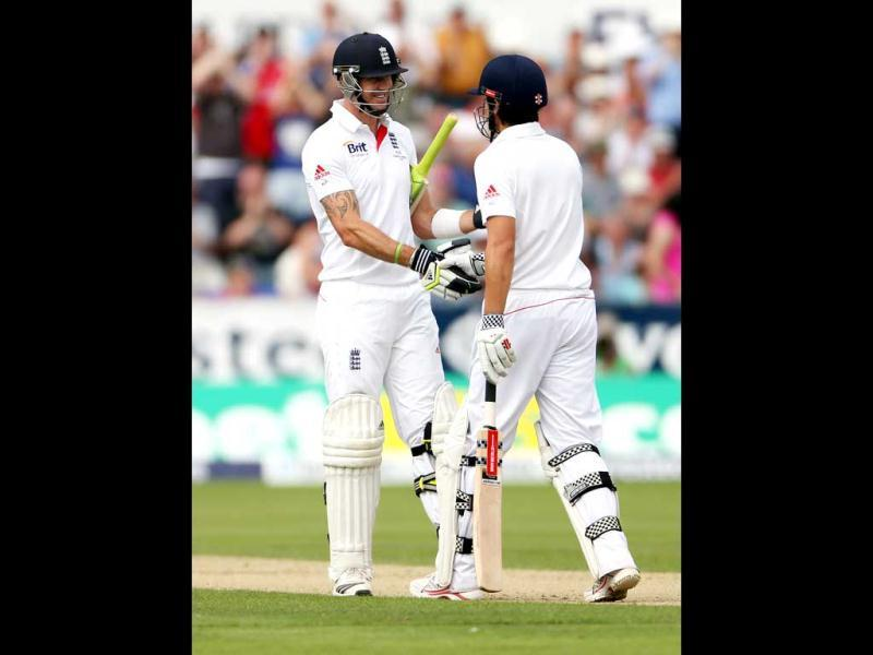 England's captain Alastair Cook (R) celebrates his 50 with Kevin Pietersen (L) during the first day of the fourth Ashes Test at the Riverside cricket ground, Chester-le-Street. (AP Photo)
